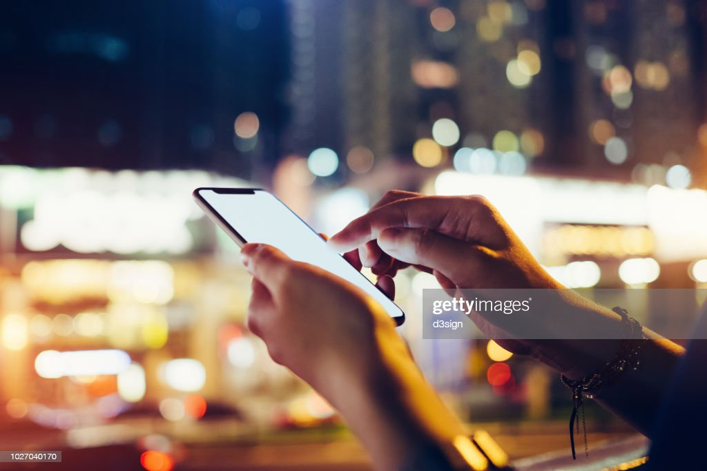 Close up of woman's hand using mobile app on smartphone to order taxi ride in busy city street at night : Stock Photo