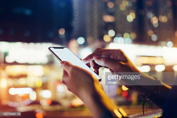 close up of woman's hand using mobile app on smartphone to order taxi ride in busy city street at night - mobile app stock-fotos und bilder