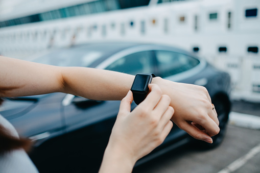 Close up of woman's hand using smart watch by the car in city - gettyimageskorea