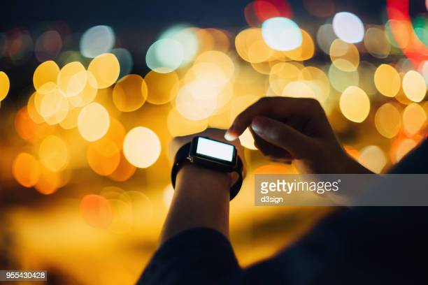 Close up of woman's hand using smart watch outdoors in city, with illuminated city street lights as background