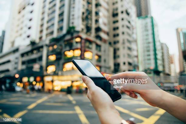 Close up of woman's hand using smartphone in city, against highrise city buildings and urban road