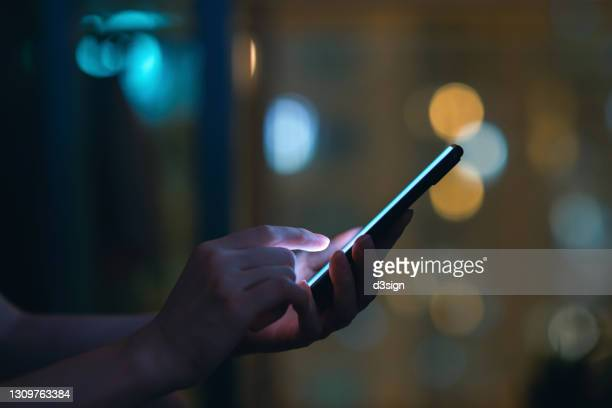 close up of woman's hand using smartphone in the dark, against illuminated city light bokeh - facebook stock pictures, royalty-free photos & images