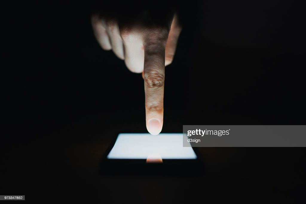 Close up of woman's hand using smartphone in the dark : Foto de stock