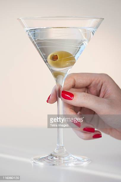 close up of woman's hand with nail polish holding martini glass with olive - martini glass stock pictures, royalty-free photos & images