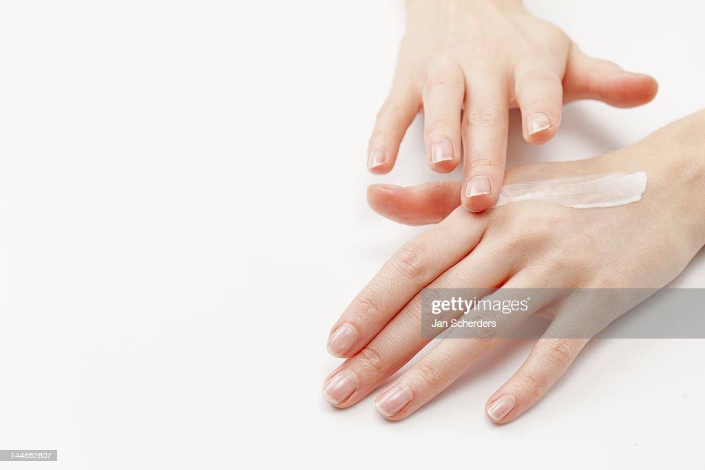 Close up of woman's hands applying  moisturizer, studio shot : Stock Photo