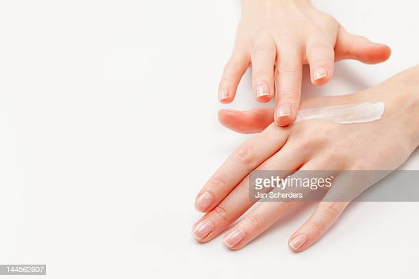 close up of woman's hands applying  moisturizer, studio shot - hand cream stock photos and pictures
