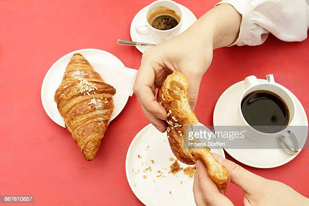 Close up of womans hands breaking croissant at sidewalk cafe
