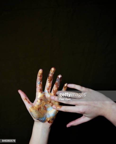 close up of womans' hands covered in gold and silver paint