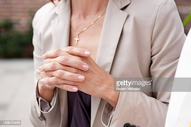 close up of woman's hands folded in prayer - christianity stock pictures, royalty-free photos & images