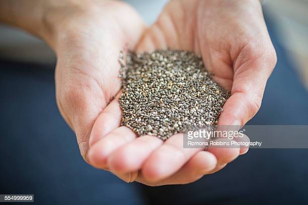 Close up of womans hands holding chia seeds