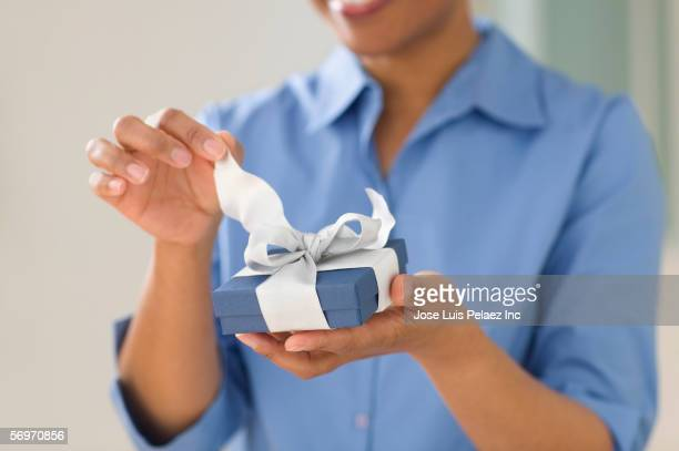 Close up of woman's hands opening gift