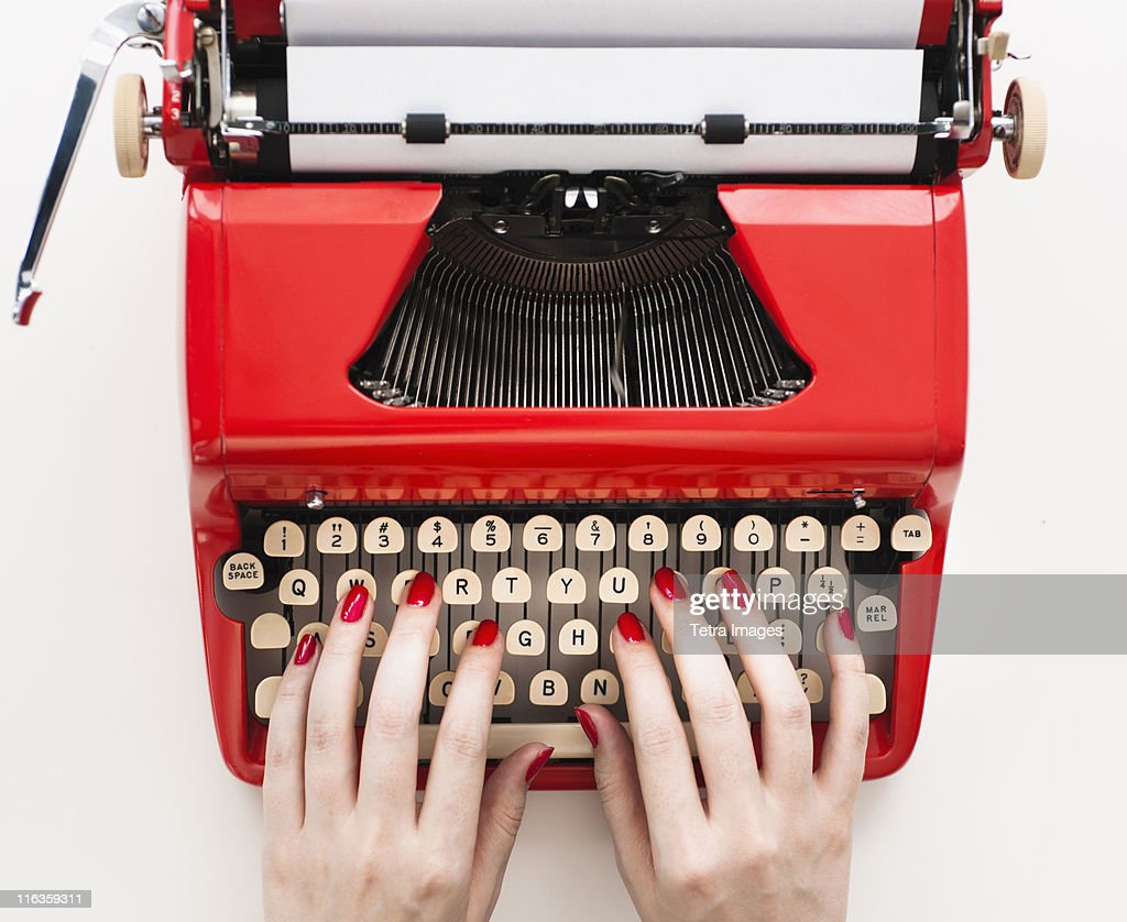 Close up of woman's hands with red nail polish typing on antique typewriter : Stock Photo