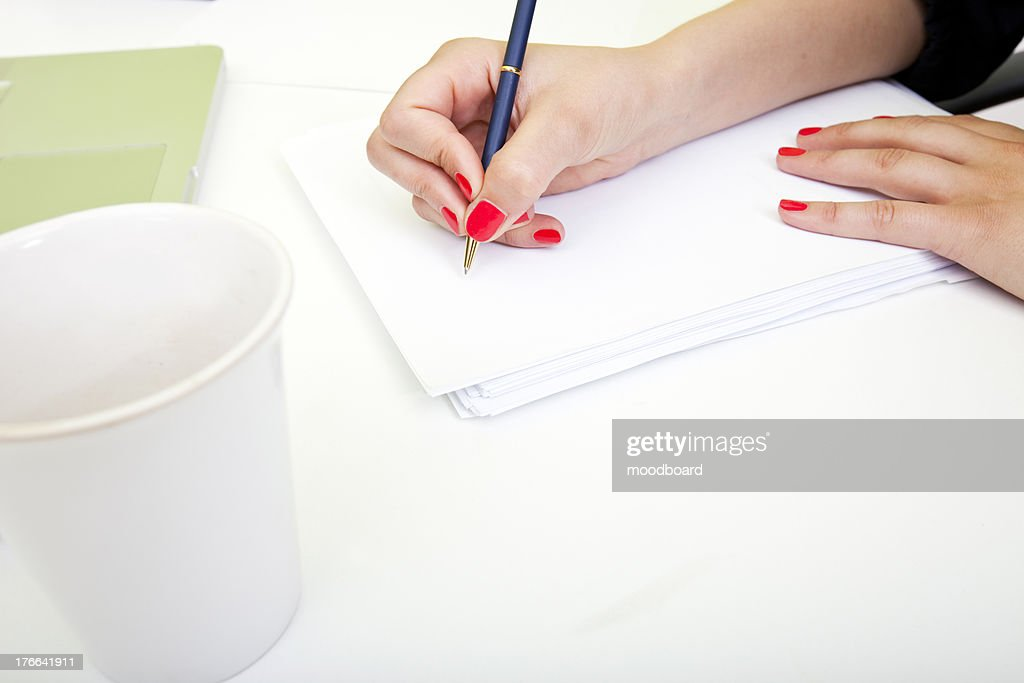 Close up of womans hands writing on paper. : Stock Photo