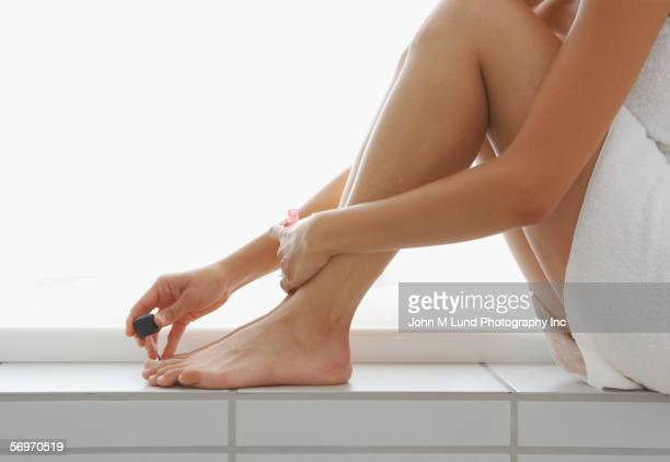 Close up of woman's lower section painting toenails