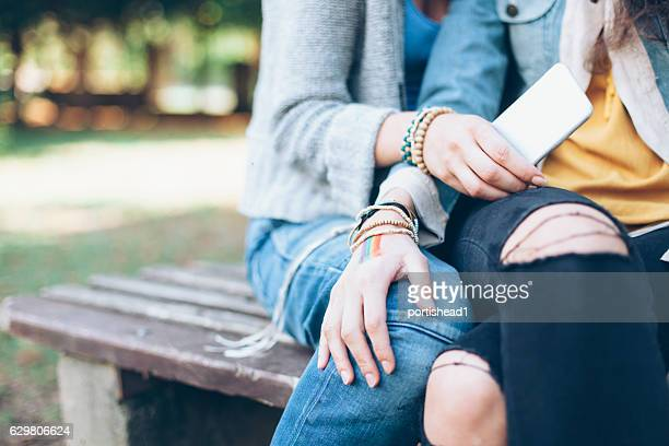 Close up of women sitting on bench and resting
