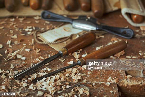 Close up of wood carving hand tools, chisels and wood shavings on a bench in a carvers workshop.