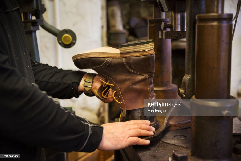 Close up of worker in a shoemakers workshop, using a machine to make a leather ankle boot. : Stock Photo