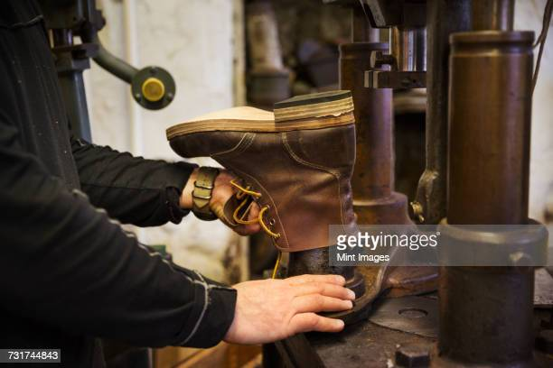 Close up of worker in a shoemakers workshop, using a machine to make a leather ankle boot.