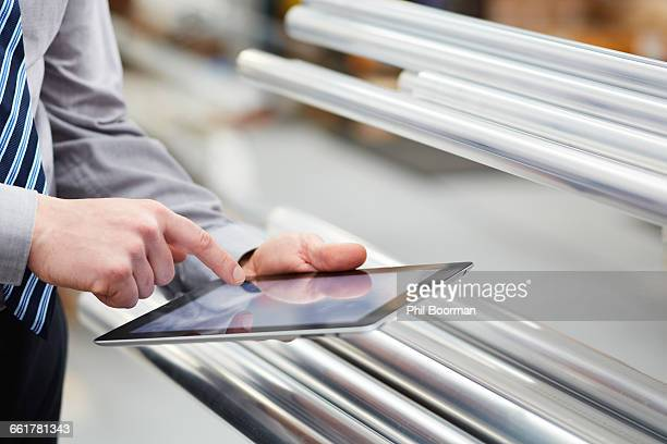 Close up of worker stock taking metal rods using digital tablet touchscreen in roller blind factory
