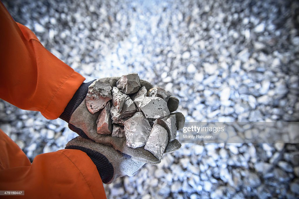 Close up of workers hands holding crushed titanium : Stock Photo