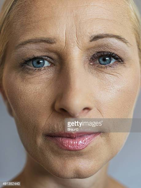 Close up of wrinkled mature woman looking at the camera.