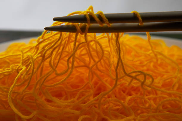 Close up of yellow wool jumbled in the knitting needles in the form of maggi