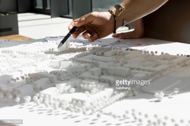 close up of young architect pointing at architectural model. - architectural model stock pictures, royalty-free photos & images