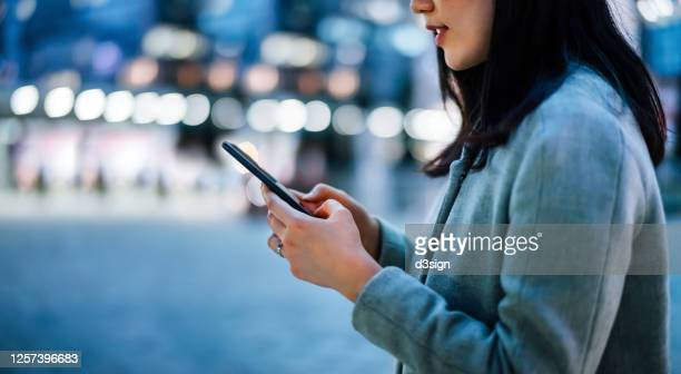 close up of young asian businesswoman using smartphone while commuting in downtown city street, with illuminated city street lights in background - facebook stock pictures, royalty-free photos & images