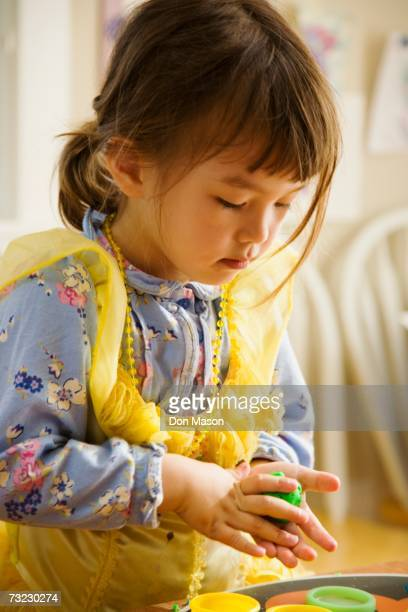Close up of young Asian girl playing with clay