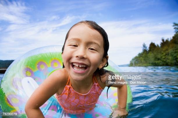 Close up of young Asian girl smiling in inner tube in water