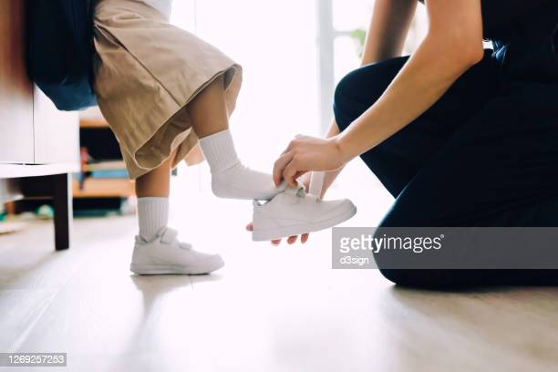 close up of young asian mother putting on shoes for her little daughter in the living room and preparing for her first day at school - school girl shoes stock pictures, royalty-free photos & images