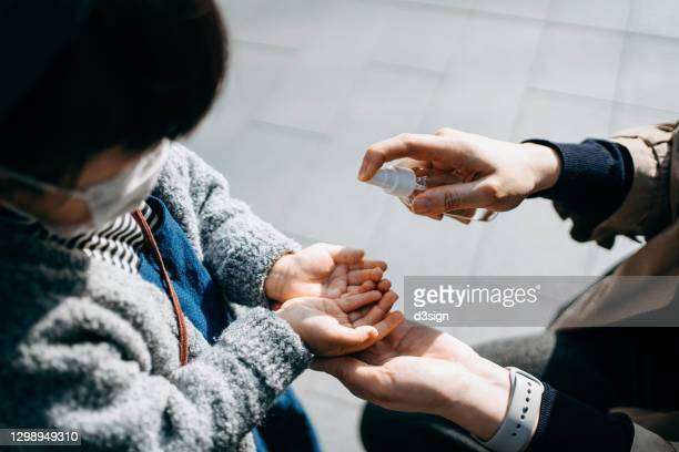 close up of young asian mother spraying hand sanitizer onto little daughter's hand outdoors, to protect and prevent from the spread of viruses. maintaining personal hygiene. the new normal of everyday life - 消毒用アルコール ストックフォトと画像