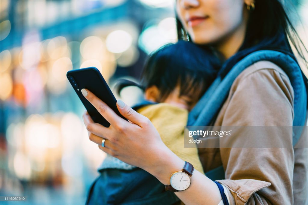 Close up of young Asian mother using smartphone in downtown city street while shopping with little daughter : ストックフォト