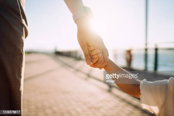 close up of young asian mother walking hand in hand with her little daughter enjoying family bonding time in a park along the promenade at sunset - childhood stock pictures, royalty-free photos & images