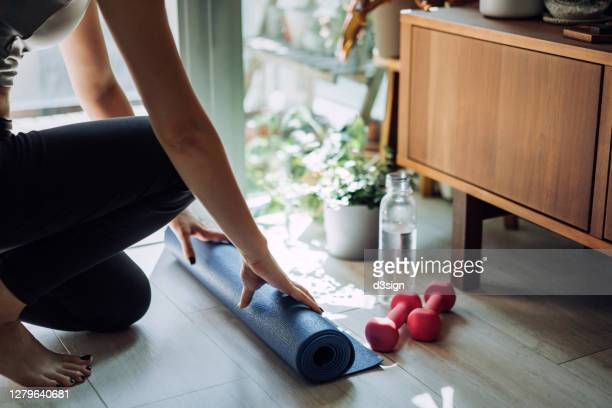 close up of young asian sports woman practicing yoga / exercising at home. unrolling yoga mat, getting prepare to work out in the fresh bright morning - 自己改善 ストックフォトと画像