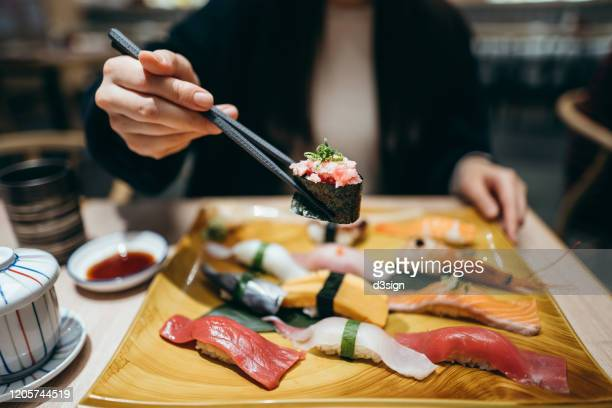 close up of young asian woman eating freshly made sushi with side dish and green tea in a japanese restaurant - japan stock pictures, royalty-free photos & images
