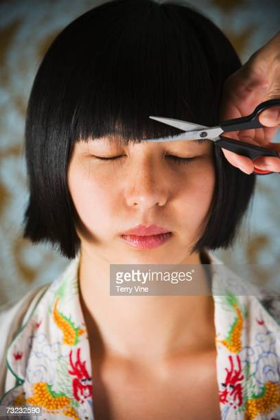 close up of young asian woman having bangs trimmed - bangs hair stock pictures, royalty-free photos & images