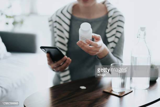 close up of young asian woman holding a pill bottle, consulting to her family doctor online in a virtual appointment over the smartphone at home - prescription medicine stock pictures, royalty-free photos & images