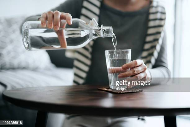 close up of young asian woman pouring water from bottle into the glass on a coffee table at home. healthy lifestyle and stay hydrated - thirsty stock pictures, royalty-free photos & images