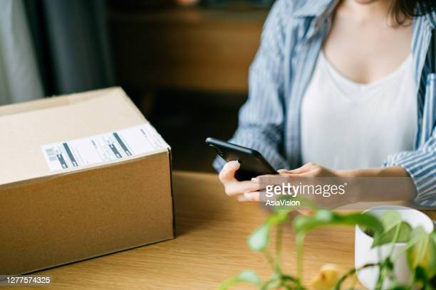 close up of young asian woman preparing a parcel for delivery using mobile app device on smartphone at home. technology makes life so much easier - returning merchandise stock pictures, royalty-free photos & images
