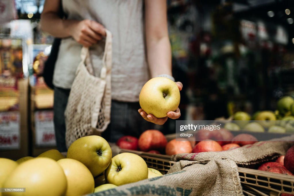 Close up of young Asian woman shopping for fresh organic fruits in farmer's market with a cotton mesh eco bag. Environmentally friendly and zero waste concept : Stockfoto