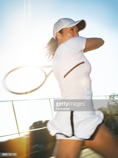 Close up of young asian woman tennis player hitting an open stance forehand