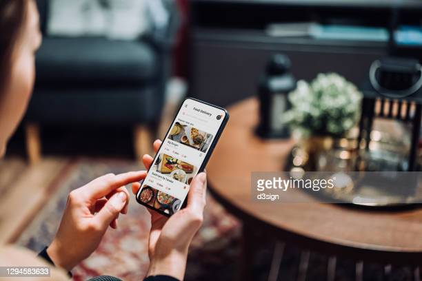 close up of young asian woman using meal delivery service and ordering food online with mobile app on smartphone while sitting on the sofa in the living room at a cozy home - graphical user interface stock pictures, royalty-free photos & images