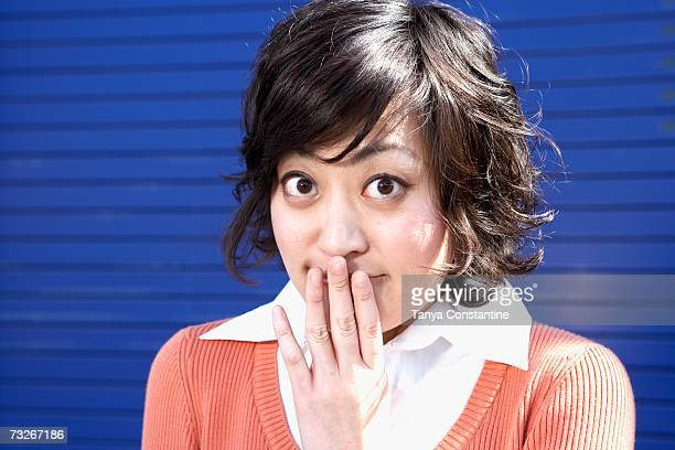 close up of young asian woman with hand over mouth outdoors - embarrassment stock pictures, royalty-free photos & images