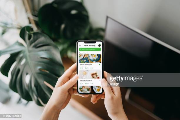 close up of young asian woman's hand using meal delivery service and ordering food online with smartphone in the living room at home, against green potted plants - portable information device stock pictures, royalty-free photos & images