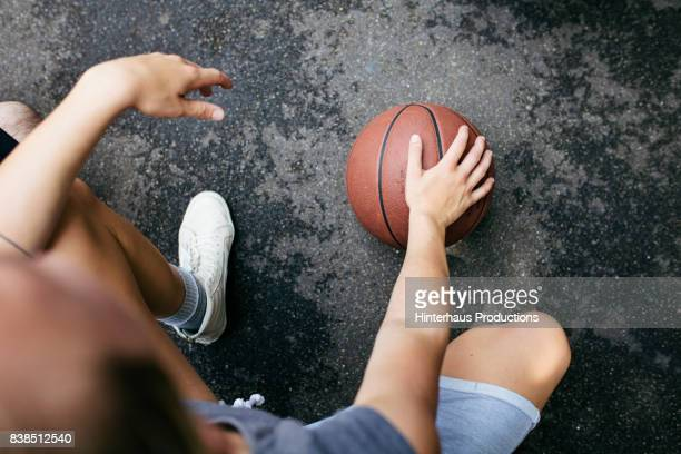 Close up Of Young Athlete Kneeling With Basketball