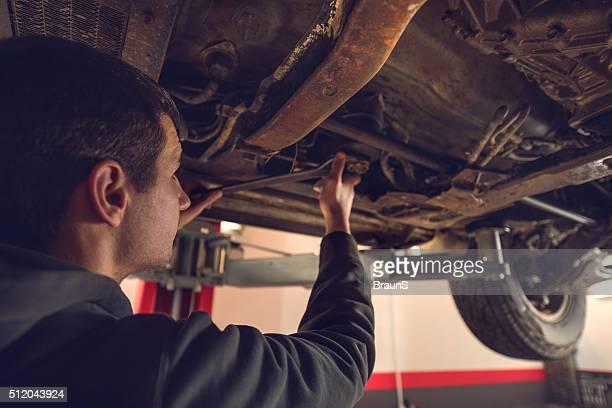 Nahaufnahme junger Auto Mechaniker reparieren Gehäuse mit dem Auto.