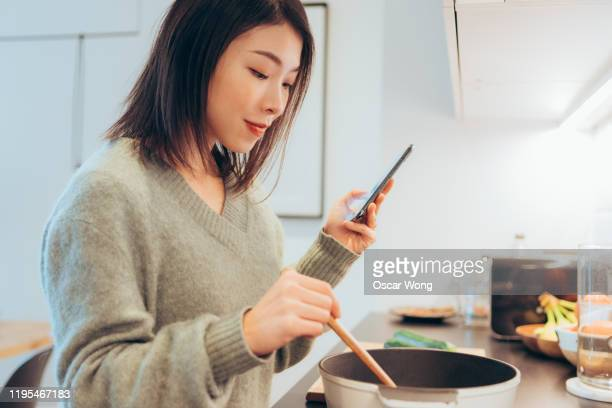 close up of young beautiful woman cooking and following recipes on smartphone in kitchen at home - woman texting stockfoto's en -beelden