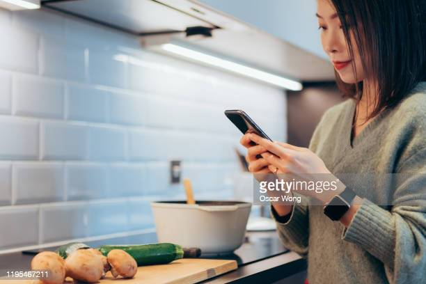close up of young beautiful woman preparing ingredients for cooking and checking recipes on smartphone in the kitchen at home - intelligence stock pictures, royalty-free photos & images