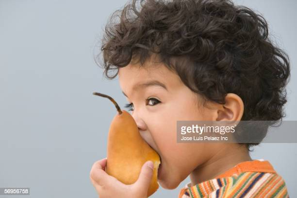 Close up of young boy eating pear